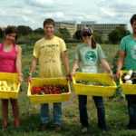 Students stand with their harvested vegetables